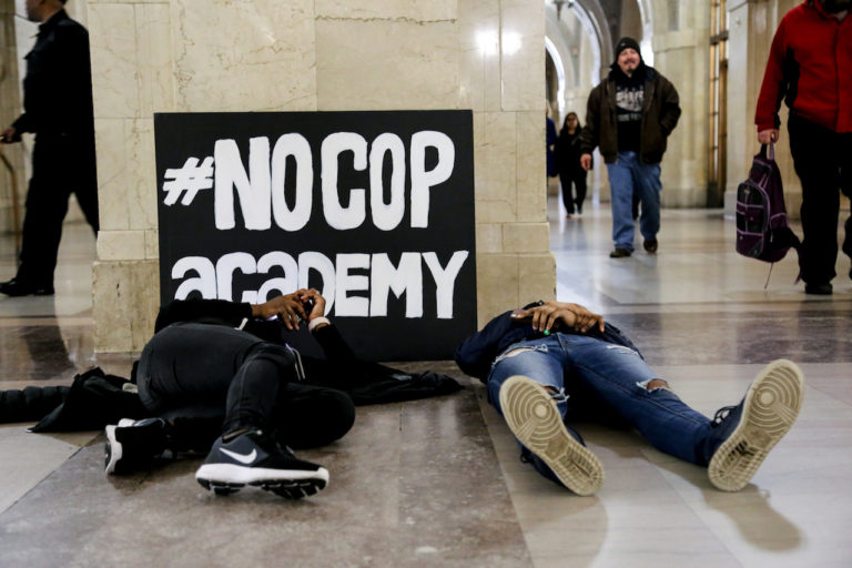 Young activists participating in a die-in at a #NoCopAcademy protest at City Hall