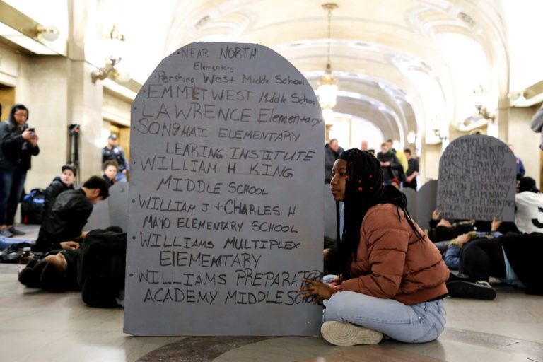 A young activist poses with the names of closed schools during a #NoCopAcademy protest at City Hall